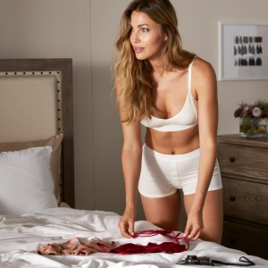 Woman in white underwear trying on lingerie- Intimates Subscription