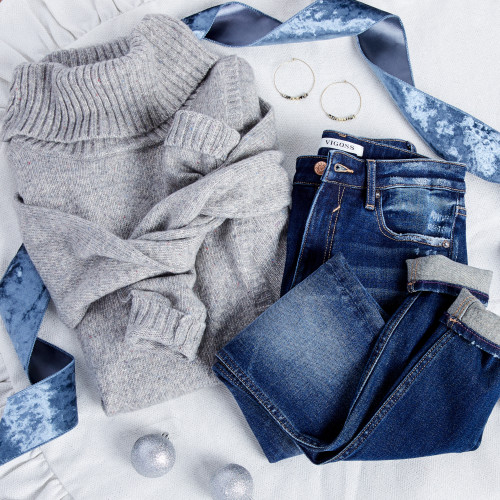 image of grey sweater, cuffed blue jeans, hoop earrings, holiday ornaments, and ribbon laying on a white background