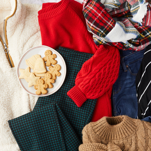 image of plaid pants, ivory quarter-zip sweater, red knit sweater, plaid scarf, jeans, and tan cable knit sweater laid out with plate of holiday sugar cookies